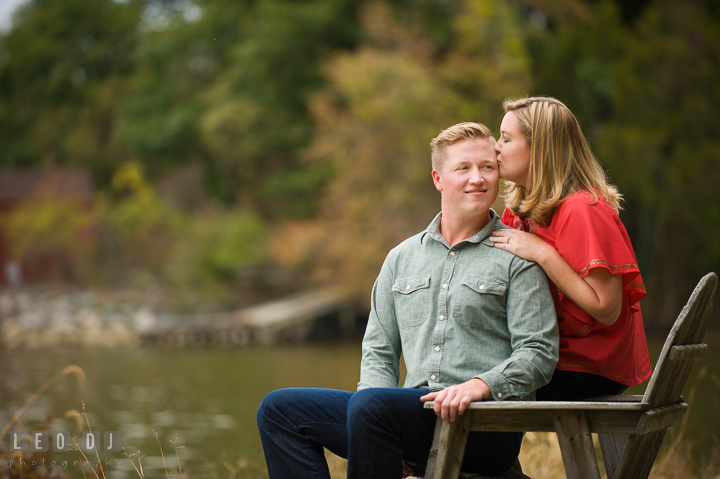 Engaged girl sitting on adirondack kissing her fiancé. Chestertown Eastern Shore Maryland pre-wedding engagement photo session by the water, by wedding photographers of Leo Dj Photography. http://leodjphoto.com