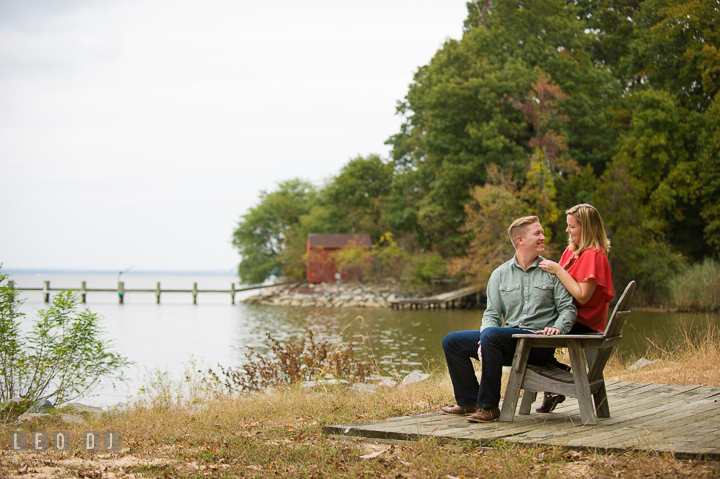 Engaged couple sitting on adirondack chair at a park with beautiful water view. Chestertown Eastern Shore Maryland pre-wedding engagement photo session by the water, by wedding photographers of Leo Dj Photography. http://leodjphoto.com