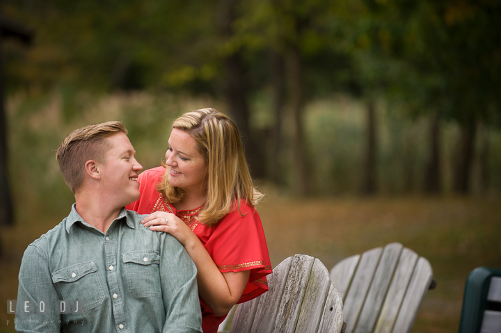 Engaged guy sitting on adirondack chair looking at his fiancé and smiling. Chestertown Eastern Shore Maryland pre-wedding engagement photo session by the water, by wedding photographers of Leo Dj Photography. http://leodjphoto.com