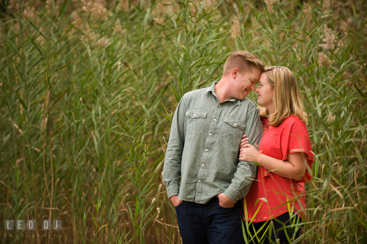 Engaged couple cuddling on the beach by tall grasses. Chestertown Eastern Shore Maryland pre-wedding engagement photo session by the water, by wedding photographers of Leo Dj Photography. http://leodjphoto.com