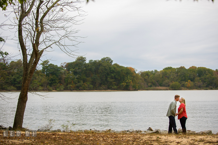 Engaged couple kissing at a park with beautiful view of the water. Chestertown Eastern Shore Maryland pre-wedding engagement photo session by the water, by wedding photographers of Leo Dj Photography. http://leodjphoto.com