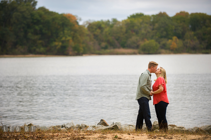 Engaged guy kissing his fiancée on the beach. Chestertown Eastern Shore Maryland pre-wedding engagement photo session by the water, by wedding photographers of Leo Dj Photography. http://leodjphoto.com