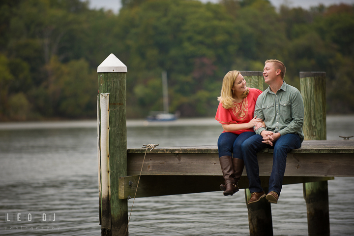 Engaged couple sitting on the dock laughing together. Chestertown Eastern Shore Maryland pre-wedding engagement photo session by the water, by wedding photographers of Leo Dj Photography. http://leodjphoto.com