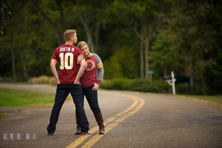 Engaged couple wearing Washington Redskins football shirt and jersey posing on the street. Chestertown Eastern Shore Maryland pre-wedding engagement photo session by the water, by wedding photographers of Leo Dj Photography. http://leodjphoto.com