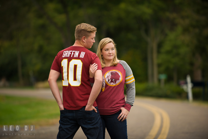 Engaged girl and her fiancé wearing Washington Redskins football shirt and jersey posing on the street. Chestertown Eastern Shore Maryland pre-wedding engagement photo session by the water, by wedding photographers of Leo Dj Photography. http://leodjphoto.com