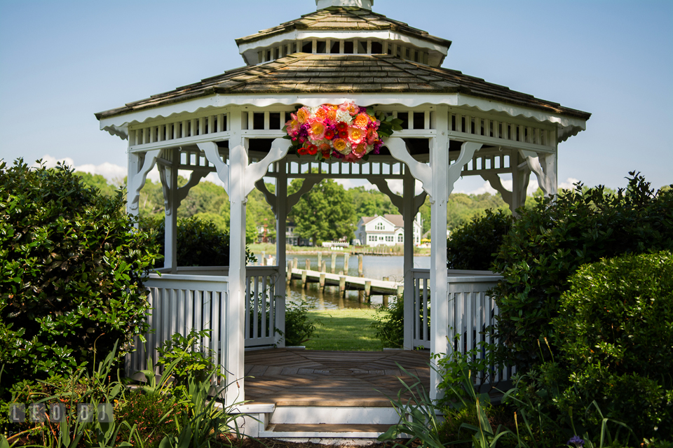 Bold and vibrant colored peonies, roses, gerberas, and proteas flower decor on gazebo designed by Intrigue Design and Decor. Kent Manor Inn, Kent Island, Eastern Shore Maryland, wedding ceremony and getting ready photos, by wedding photographers of Leo Dj Photography. http://leodjphoto.com