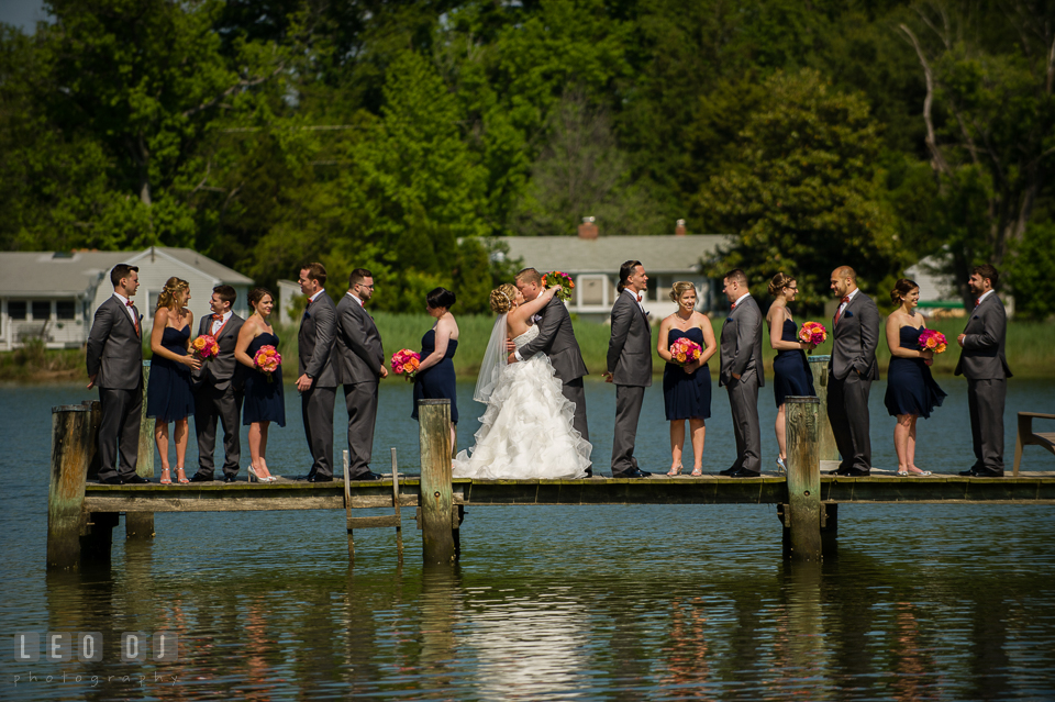 Bride and Groom kissing while the wedding party is on the dock . Kent Manor Inn, Kent Island, Eastern Shore Maryland, wedding ceremony and getting ready photos, by wedding photographers of Leo Dj Photography. http://leodjphoto.com