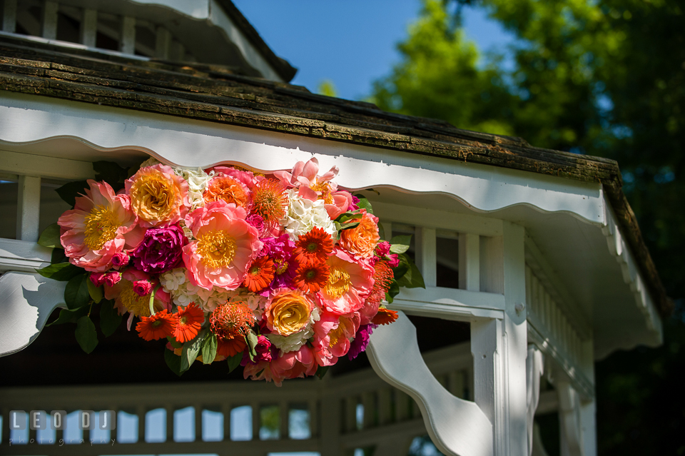 Floral decor of bold and vibrant colored peonies, roses, gerberas, and proteas on gazebo designed florist by Intrigue Design and Decor. Kent Manor Inn, Kent Island, Eastern Shore Maryland, wedding ceremony and getting ready photos, by wedding photographers of Leo Dj Photography. http://leodjphoto.com