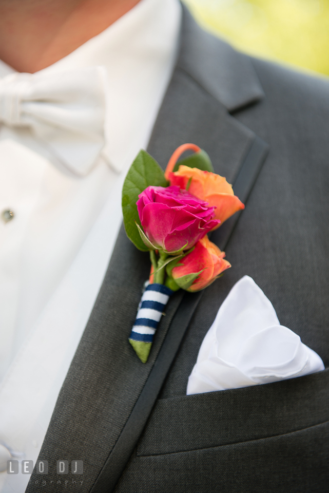 Groom's boutonniere using dark pink and orange roses. Kent Manor Inn, Kent Island, Eastern Shore Maryland, wedding ceremony and getting ready photos, by wedding photographers of Leo Dj Photography. http://leodjphoto.com