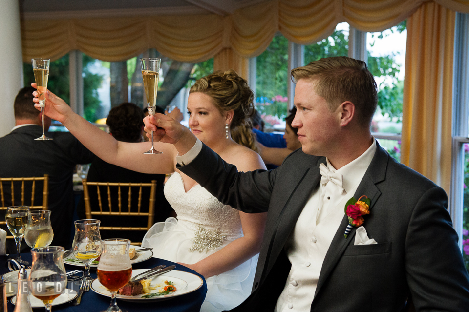 Bride and Groom raised their champagne glasses during the toast. Kent Manor Inn, Kent Island, Eastern Shore Maryland, wedding reception and ceremony photo, by wedding photographers of Leo Dj Photography. http://leodjphoto.com
