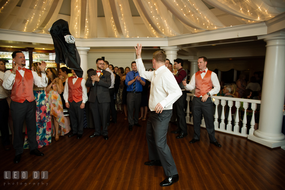 Groom threw jacket to Best Man before getting garter from Bride. Kent Manor Inn, Kent Island, Eastern Shore Maryland, wedding reception and ceremony photo, by wedding photographers of Leo Dj Photography. http://leodjphoto.com