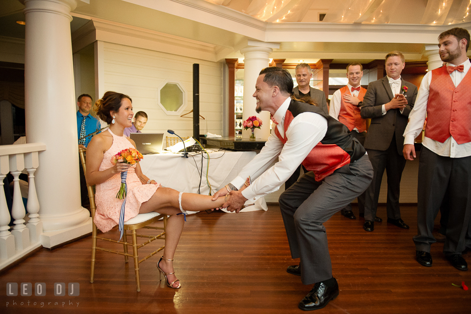 Best Man putting garter on his fianceé. Kent Manor Inn, Kent Island, Eastern Shore Maryland, wedding reception and ceremony photo, by wedding photographers of Leo Dj Photography. http://leodjphoto.com
