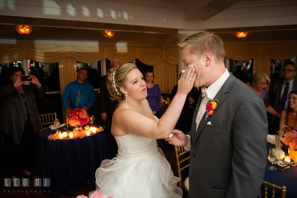 Bride slapped cake icing on Groom's cheek during cake cutting. Kent Manor Inn, Kent Island, Eastern Shore Maryland, wedding reception and ceremony photo, by wedding photographers of Leo Dj Photography. http://leodjphoto.com