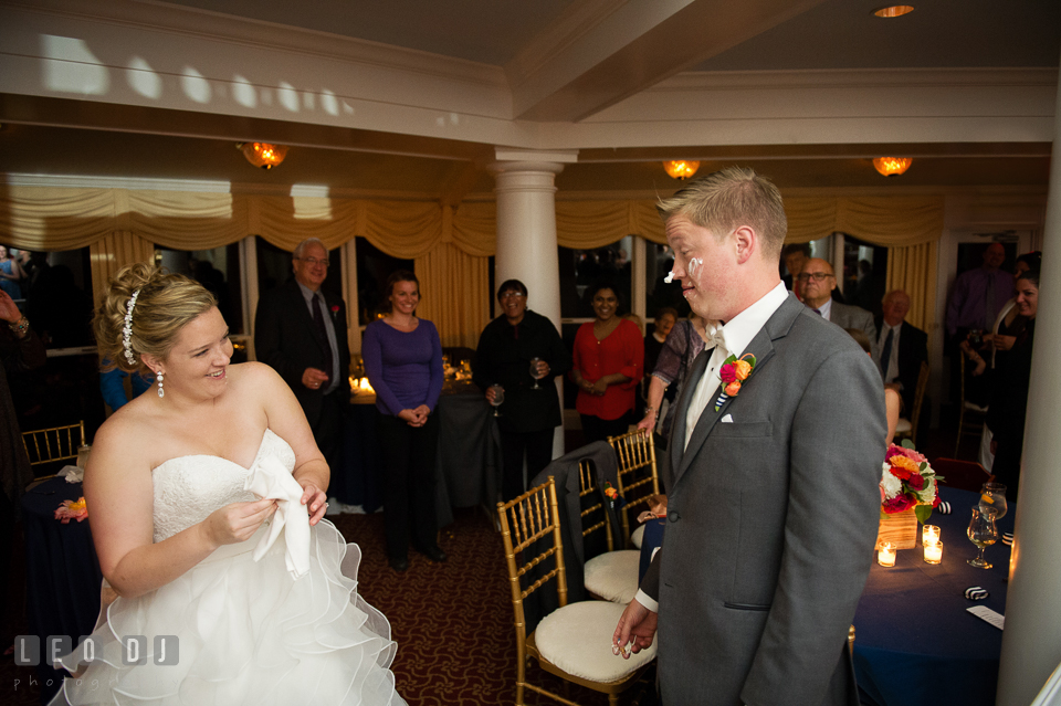 Bride and guests laughed seeing Groom with icing on his face after cake cutting. Kent Manor Inn, Kent Island, Eastern Shore Maryland, wedding reception and ceremony photo, by wedding photographers of Leo Dj Photography. http://leodjphoto.com