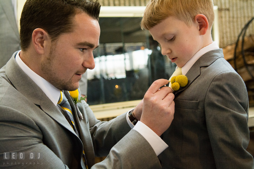 Groom putting on boutonniere on the ring bearer boy. Maryland Yacht Club wedding at Pasadena Maryland, by wedding photographers of Leo Dj Photography. http://leodjphoto.com