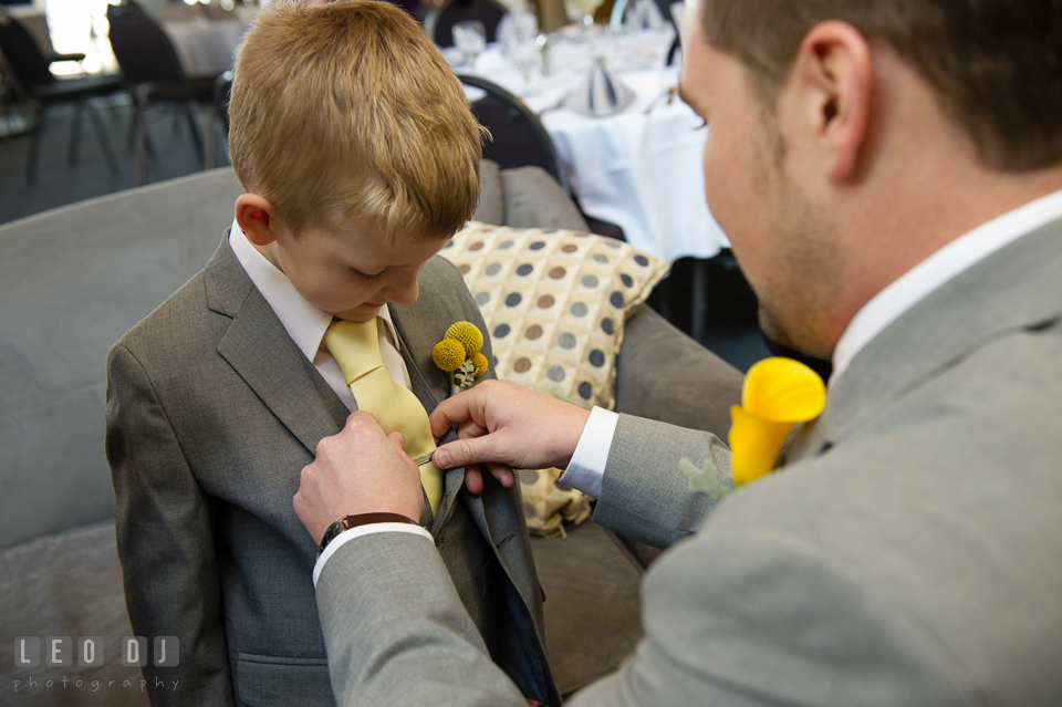 Groom put tie clip for the ring bearer boy. Maryland Yacht Club wedding at Pasadena Maryland, by wedding photographers of Leo Dj Photography. http://leodjphoto.com