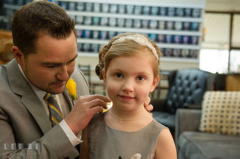 Groom putting on necklace gift around flower girl's neck. Maryland Yacht Club wedding at Pasadena Maryland, by wedding photographers of Leo Dj Photography. http://leodjphoto.com