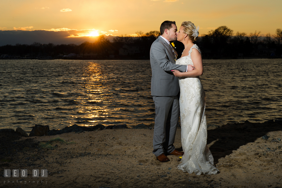 Bride and Groom kissing by the water during sunset. Maryland Yacht Club wedding at Pasadena Maryland, by wedding photographers of Leo Dj Photography. http://leodjphoto.com
