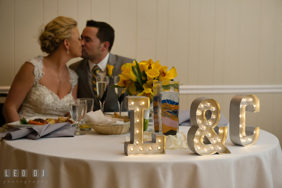 Bride and Groom kissing behind their sweetheart table. Maryland Yacht Club wedding at Pasadena Maryland, by wedding photographers of Leo Dj Photography. http://leodjphoto.com
