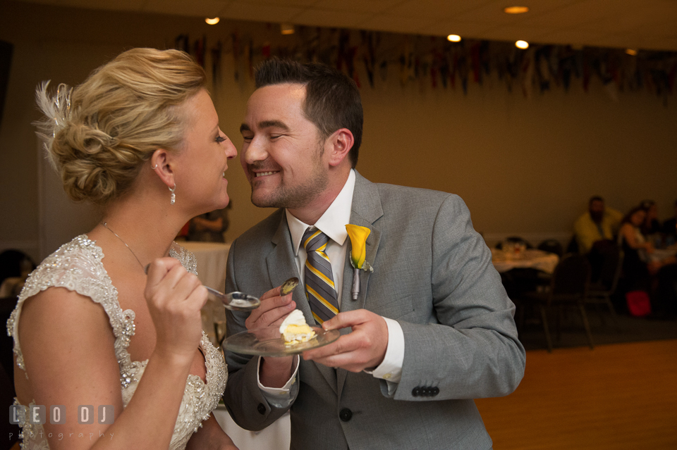 Bride and Groom kissing and feeding cake to each other. Maryland Yacht Club wedding at Pasadena Maryland, by wedding photographers of Leo Dj Photography. http://leodjphoto.com