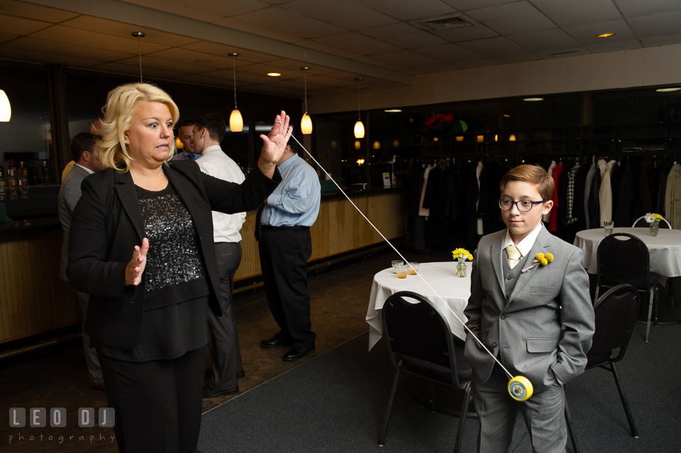 Ring bearer boy watching her aunt playing yo-yo. Maryland Yacht Club wedding at Pasadena Maryland, by wedding photographers of Leo Dj Photography. http://leodjphoto.com