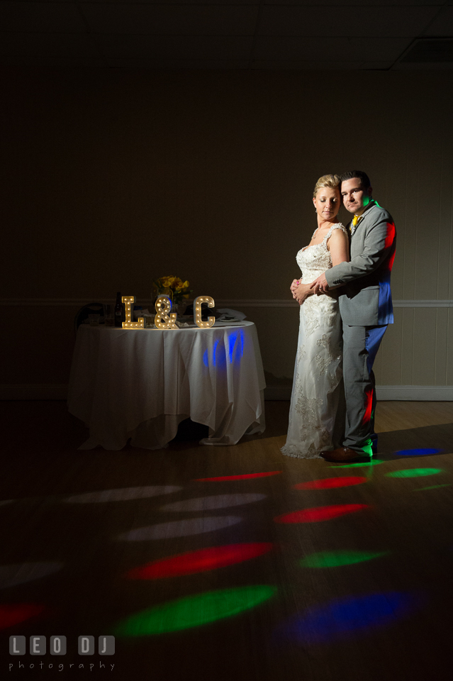 Bride and Groom posing by their sweetheart table lighted with colorful lights from the DJ. Maryland Yacht Club wedding at Pasadena Maryland, by wedding photographers of Leo Dj Photography. http://leodjphoto.com