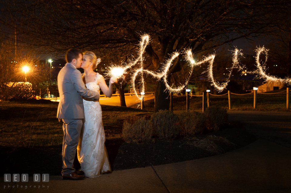 Bride and Groom kissing with sparklers writing Love. Maryland Yacht Club wedding at Pasadena Maryland, by wedding photographers of Leo Dj Photography. http://leodjphoto.com