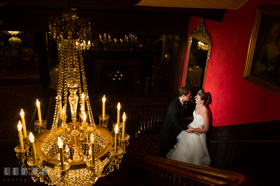 The Mansion at Valley Country Club Groom cuddling Bride by antique chandelier photo by Leo Dj Photography