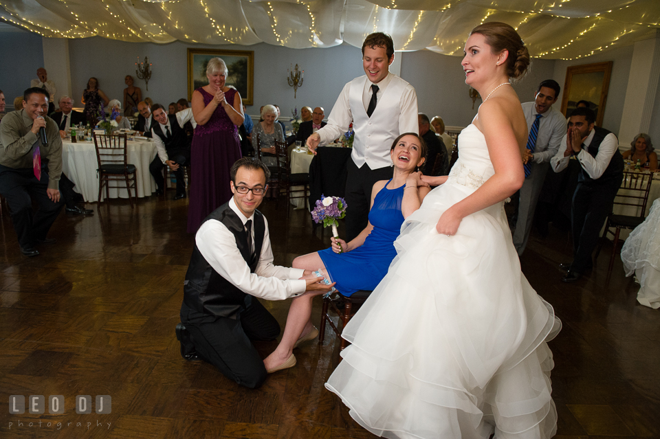 The Mansion at Valley Country Club Bridesmaid laughed as Groomsman put garter photo