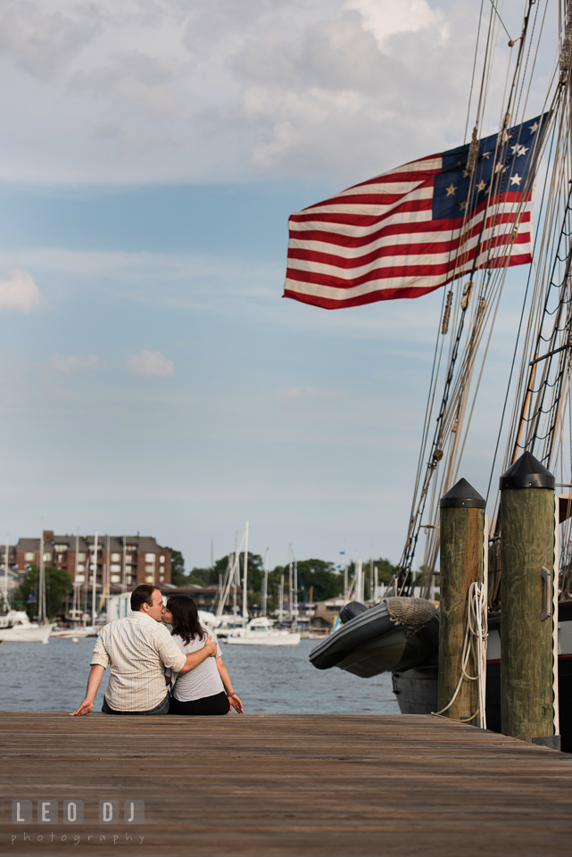 Engaged couple kissing on the dock with vintage American flag from a tall ship. Annapolis Eastern Shore Maryland pre-wedding engagement photo session at downtown, by wedding photographers of Leo Dj Photography. http://leodjphoto.com