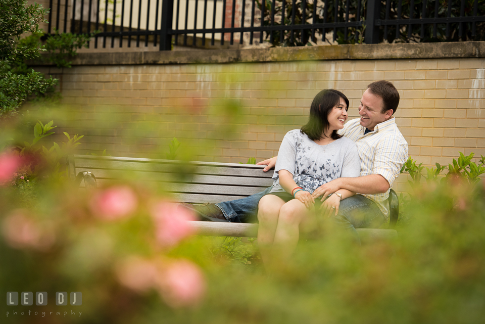 Engaged couple sitting together on a bench, laughing. Annapolis Eastern Shore Maryland pre-wedding engagement photo session at downtown, by wedding photographers of Leo Dj Photography. http://leodjphoto.com