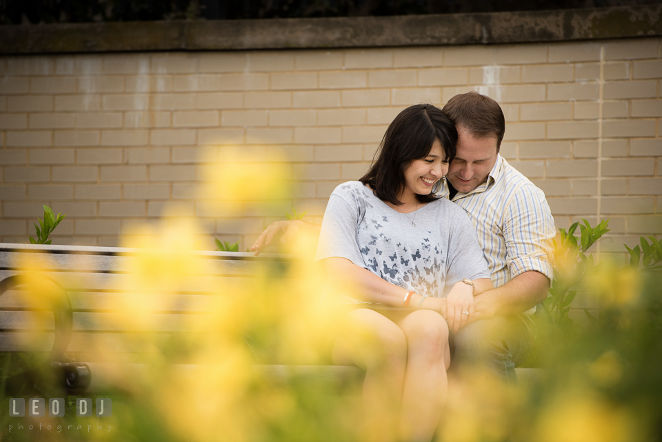 Engaged girl sitting on bench and cuddling together with her fiance. Annapolis Eastern Shore Maryland pre-wedding engagement photo session at downtown, by wedding photographers of Leo Dj Photography. http://leodjphoto.com