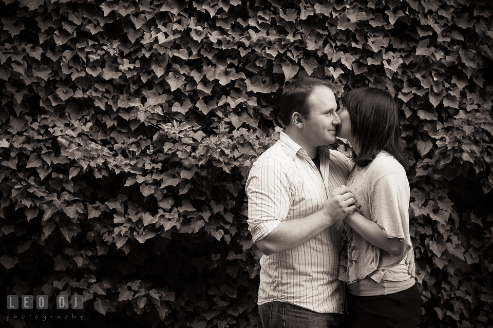 Engaged man kissed by his fiancee, by a wall filled with ivy. Annapolis Eastern Shore Maryland pre-wedding engagement photo session at downtown, by wedding photographers of Leo Dj Photography. http://leodjphoto.com