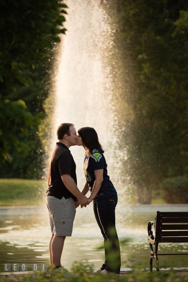 Engaged girl kissing her fiance by the fountain. Quiet Waters Park Annapolis Maryland pre-wedding engagement photo session, by wedding photographers of Leo Dj Photography. http://leodjphoto.com