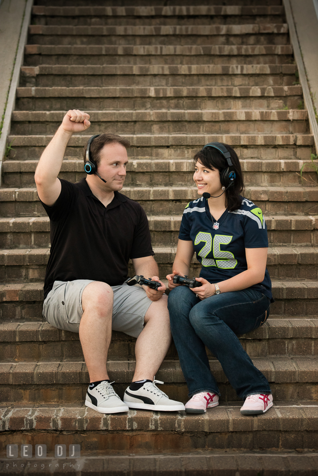 Engaged girl with her fiancé sitting on the stairs using video game controller and headset. Quiet Waters Park Annapolis Maryland pre-wedding engagement photo session, by wedding photographers of Leo Dj Photography. http://leodjphoto.com