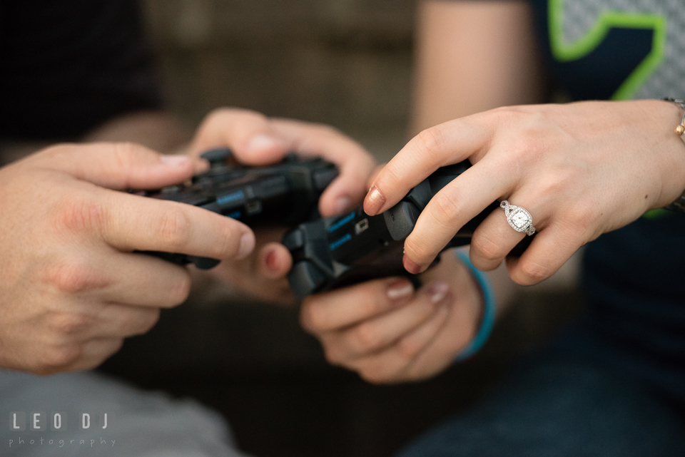 Engaged girl with her fiance holding video game controller, showing her beautiful diamond engagement ring. Quiet Waters Park Annapolis Maryland pre-wedding engagement photo session, by wedding photographers of Leo Dj Photography. http://leodjphoto.com