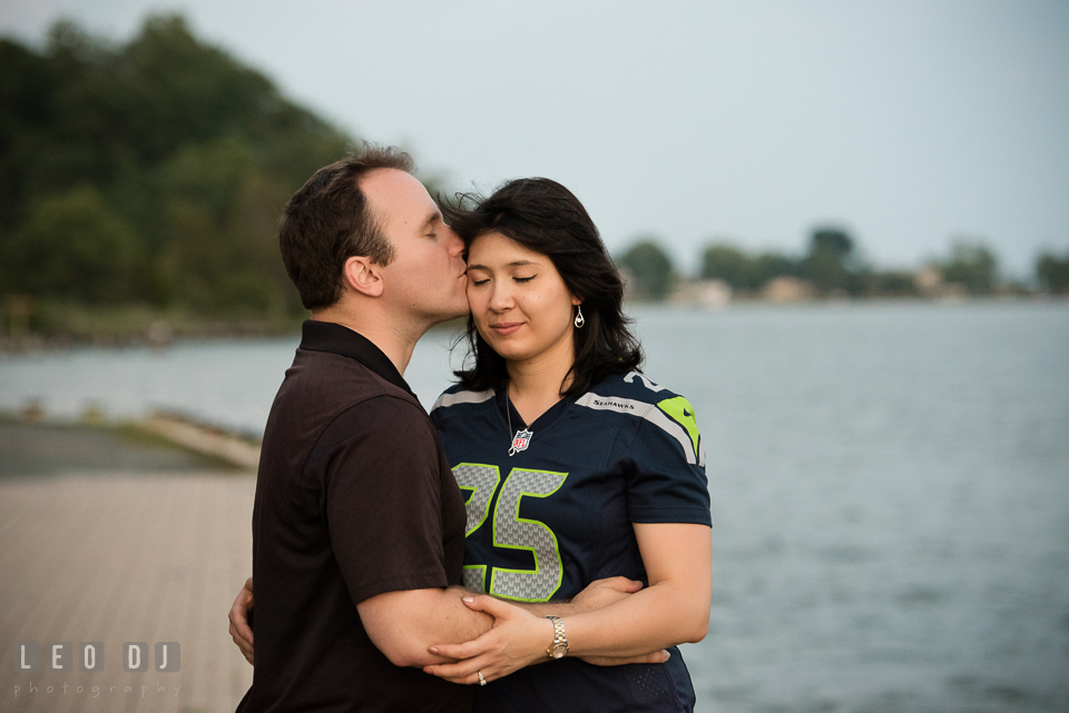 Engaged man holding and kissing his fiancee. Quiet Waters Park Annapolis Maryland pre-wedding engagement photo session, by wedding photographers of Leo Dj Photography. http://leodjphoto.com