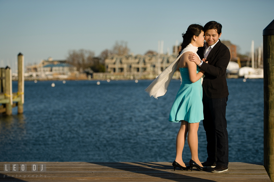 Engaged couple holding each other on the dock. Annapolis Eastern Shore Maryland pre-wedding engagement photo session at downtown, by wedding photographers of Leo Dj Photography. http://leodjphoto.com