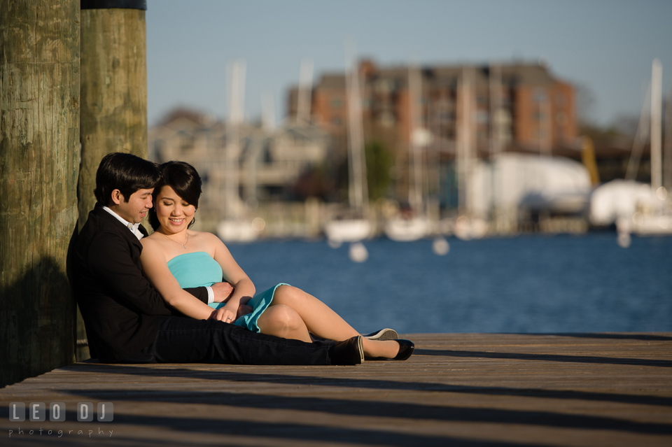 Engaged girl sitting on the dock and embraced by her fiance. Annapolis Eastern Shore Maryland pre-wedding engagement photo session at downtown, by wedding photographers of Leo Dj Photography. http://leodjphoto.com