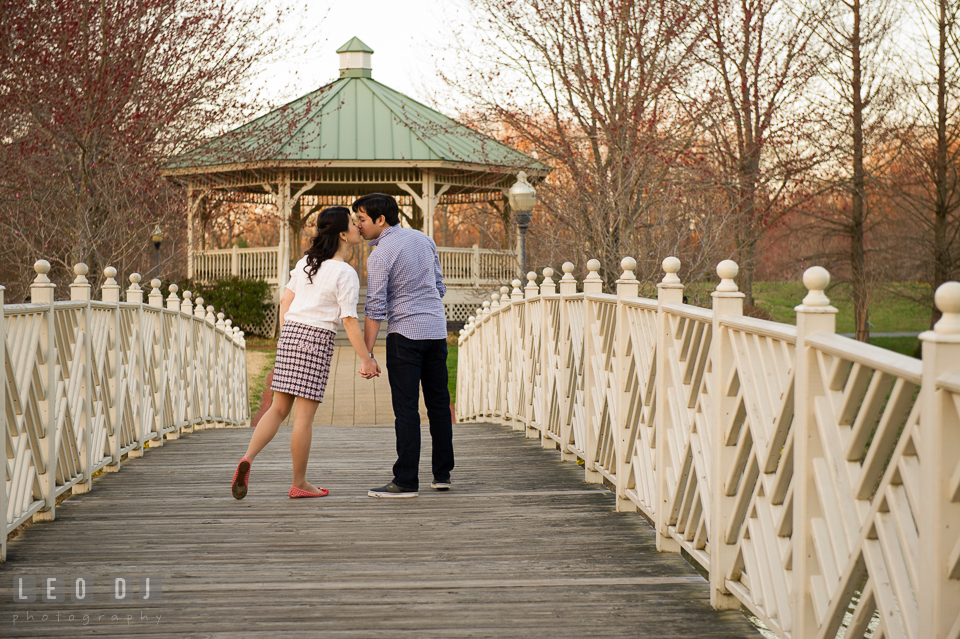 Engaged couple kissing on the bridge. Quiet Waters Park Annapolis Maryland pre-wedding engagement photo session, by wedding photographers of Leo Dj Photography. http://leodjphoto.com