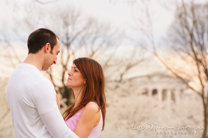 Engaged couple looking at each other with cherry blossom trees and Jefferson Memorial in the background. Washington DC Tidal Basin Cherry Blossom Pre-Wedding Engagement Photo Session by Wedding Photographer Leo Dj Photography