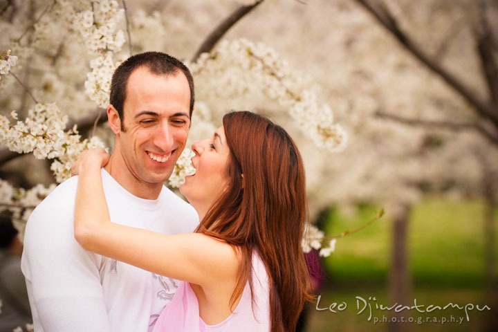 Engaged girl teasing her fiancé by the cherry blossom trees. Washington DC Tidal Basin Cherry Blossom Pre-Wedding Engagement Photo Session by Wedding Photographer Leo Dj Photography