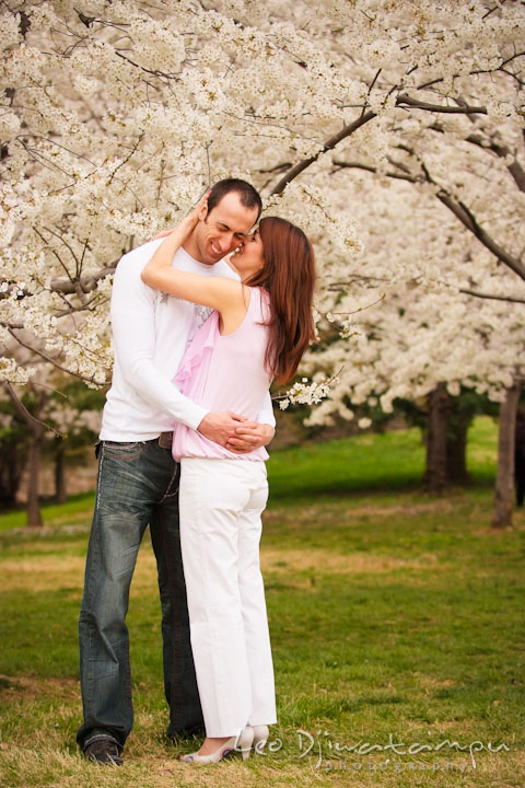 Engaged girl whispering something in her fiancé's ear. Washington DC Tidal Basin Cherry Blossom Pre-Wedding Engagement Photo Session by Wedding Photographer Leo Dj Photography