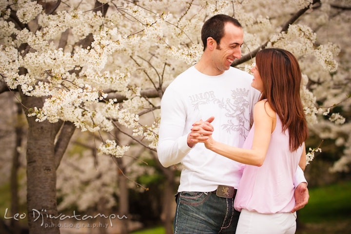 Engaged couple slow dancing by the cherry blossom trees. Washington DC Tidal Basin Cherry Blossom Pre-Wedding Engagement Photo Session by Wedding Photographer Leo Dj Photography