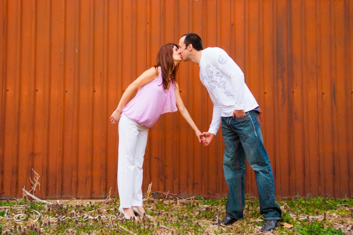 Engaged guy and girl kissing by a red metal wall. Washington DC Tidal Basin Cherry Blossom Pre-Wedding Engagement Photo Session by Wedding Photographer Leo Dj Photography