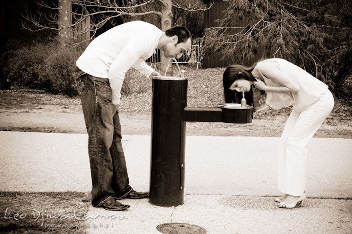 Engaged guy and girl drinking from the water fountain together. Washington DC Tidal Basin Cherry Blossom Pre-Wedding Engagement Photo Session by Wedding Photographer Leo Dj Photography