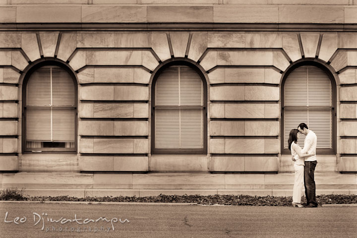 Engaged guy and girl cuddling by and old historic building. Washington DC Tidal Basin Cherry Blossom Pre-Wedding Engagement Photo Session by Wedding Photographer Leo Dj Photography