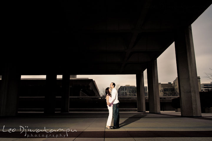 Engaged couple dancing under a huge concrete structure. Washington DC Tidal Basin Cherry Blossom Pre-Wedding Engagement Photo Session by Wedding Photographer Leo Dj Photography