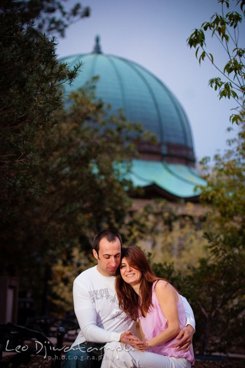 Engaged guy hugging his fiancée. Green building dome behind them. Washington DC Tidal Basin Cherry Blossom Pre-Wedding Engagement Photo Session by Wedding Photographer Leo Dj Photography