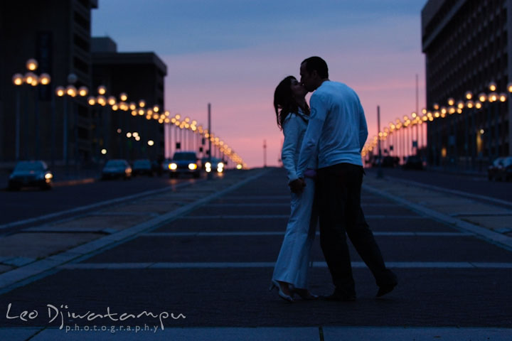 Engaged couple kissing on the street with evening sky and street lights. Washington DC Tidal Basin Cherry Blossom Pre-Wedding Engagement Photo Session by Wedding Photographer Leo Dj Photography